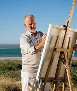 Painter outdoors with easel and supplies